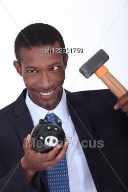 Man Hammering Open A Piggy Bank Stock Photo