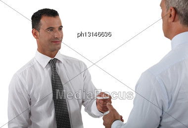 Man Handing Over His Business Card To A Potential Client Stock Photo