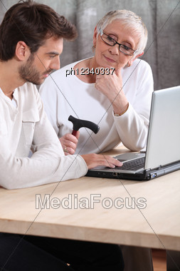 Man Helping An Elderly Lady With Her Laptop Stock Photo
