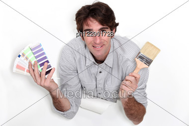 Man Holding Colour Samples And A Paintbrush Stock Photo