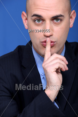 Man Holding A Finger To His Lips Stock Photo