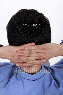 Man Holding His Hands On His Neck Stock Photo