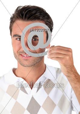 Man Holding Metallic At Symbol Over Eye Stock Photo