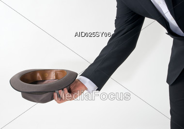 Man Holding Out Empty Hat For Money Stock Photo