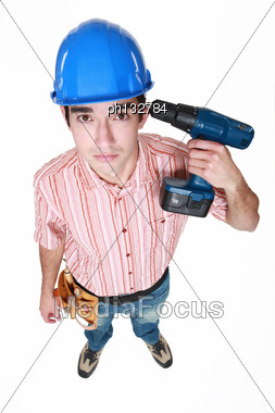 Man Holding Power Drill Against Head Stock Photo