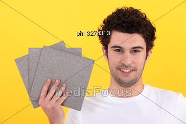 Man Holding Up Tiles Stock Photo