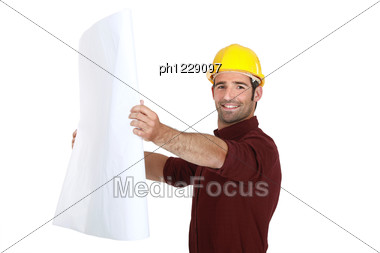Man In A Hardhat Holding Plans Stock Photo