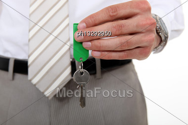 Man In A Suit Holding A Key Stock Photo