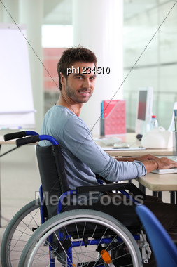 Man In Wheelchair Working At Computer Stock Photo