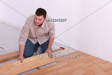 Man Laying Laminate Floor In Apartment Stock Photo