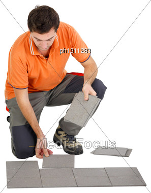 Man Laying Out Tiles On The Floor Stock Photo