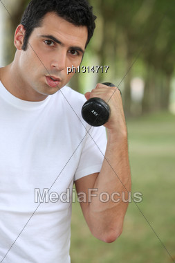 Man Lifting Dumbbell Outdoors Stock Photo