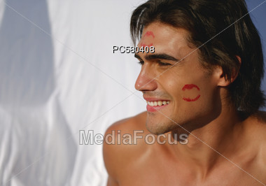 Man with Lipstick Kisses on his Face Stock Photo