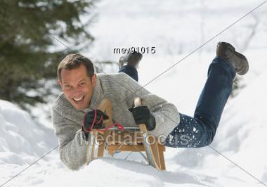 Man Lying On Sledge Stock Photo