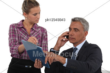 Man Making A Business Call With The Help Of His Secretary Stock Photo
