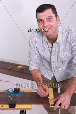 Man Marking A Floorboard With A Pencil Stock Photo