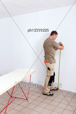 Man Measuring Wall Stock Photo