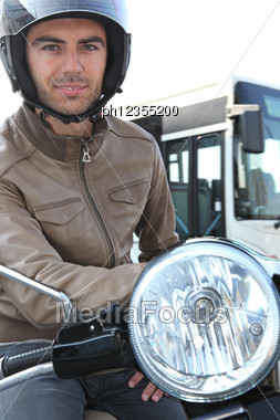 Man On A Moped With A Bus In The Background Stock Photo
