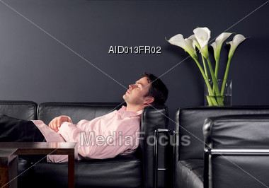 Man Napping On Black Leather Couch Stock Photo
