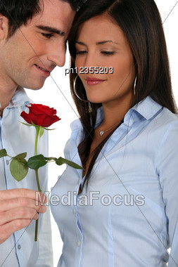 Man Offering A Rose To His Girlfriend Stock Photo