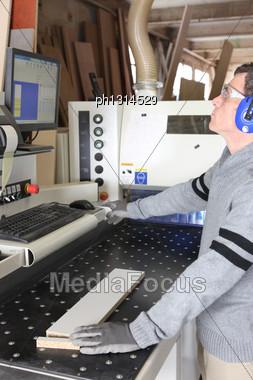 Man Operating Factory Saw Stock Photo