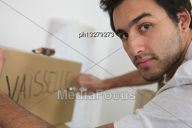Man Packing Dishes Stock Photo