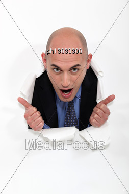 Man Peeking Through Torn Paper Hole Stock Photo