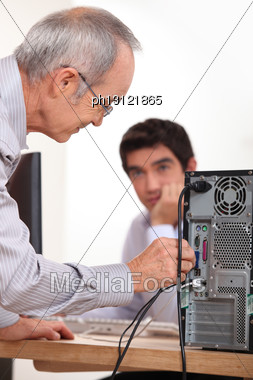 Man Plugging A Cable Into The Back Of A Hard Drive Stock Photo