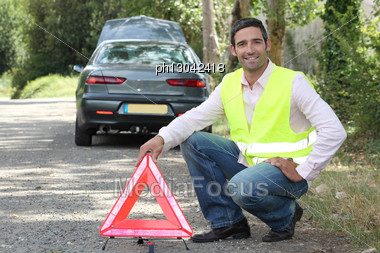 Man Putting Out A Hazard Triangle Stock Photo