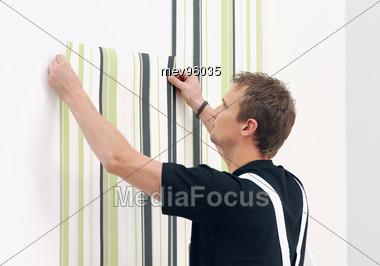 Man Putting Up Wallpaper Stock Photo