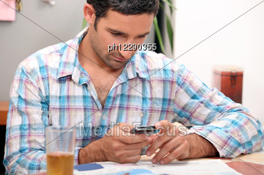 Man Reading Magazine And Sending Text Message Stock Photo
