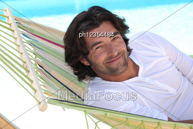 Man Resting In Hammock Next To Swimming Pool Stock Photo