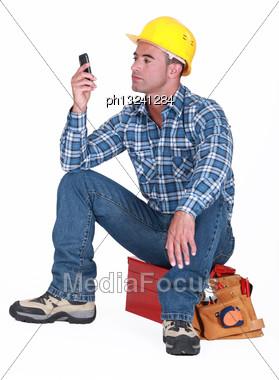 Man Sat On Tool Box Sending Text Message Stock Photo