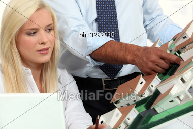 Man Showing His Assistant A Small-scale Model Stock Photo