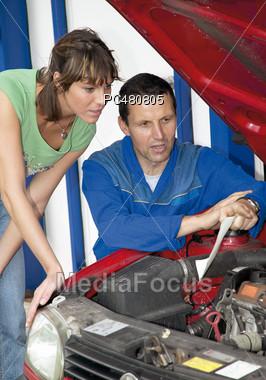 Man Showing Woman Car Repair Stock Photo