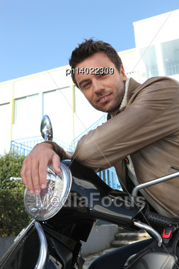 Man Sitting On Scooter Stock Photo