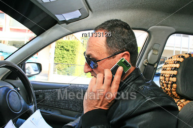 Man Speaking By Phone In Car With Business Papers Stock Photo