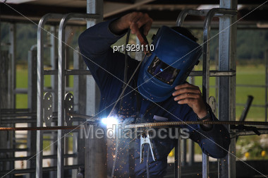 Man Spot Welding Temporary Framework In New Dairy Stock Photo