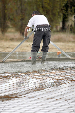 Man Spreading Concrete Foundations Stock Photo