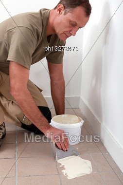 Man Spreading Tile Adhesive On Old Tiles Stock Photo