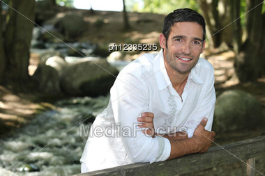 Man Standing By A Woodland Stream Stock Photo