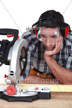 Man Staring At A Circular Saw. Stock Photo