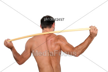 Man Stretching With Wooden Pole Stock Photo