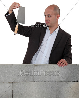 Man In Suit Holding A Trowel Behind A Brick Wall Stock Photo