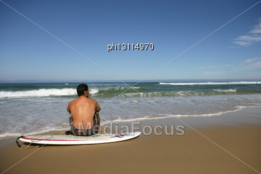 Man Taking A Break From Surfing Stock Photo