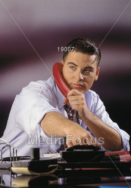 Man Tallking On Red Phone Stock Photo