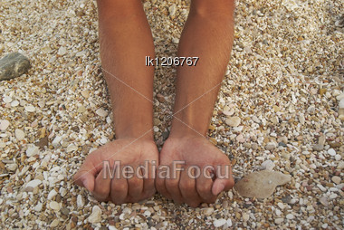 Man Tanned Hands Compressed Into Cams Against Background Of Small Stones On The Beach Stock Photo