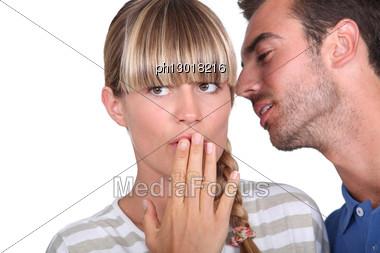 Man Telling A Secret To A Woman Stock Photo