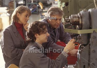 Man Training Woman On Machine, Woman Observes Stock Photo