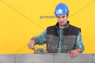 Man With Trowel Spreading Cement On Wall Stock Photo